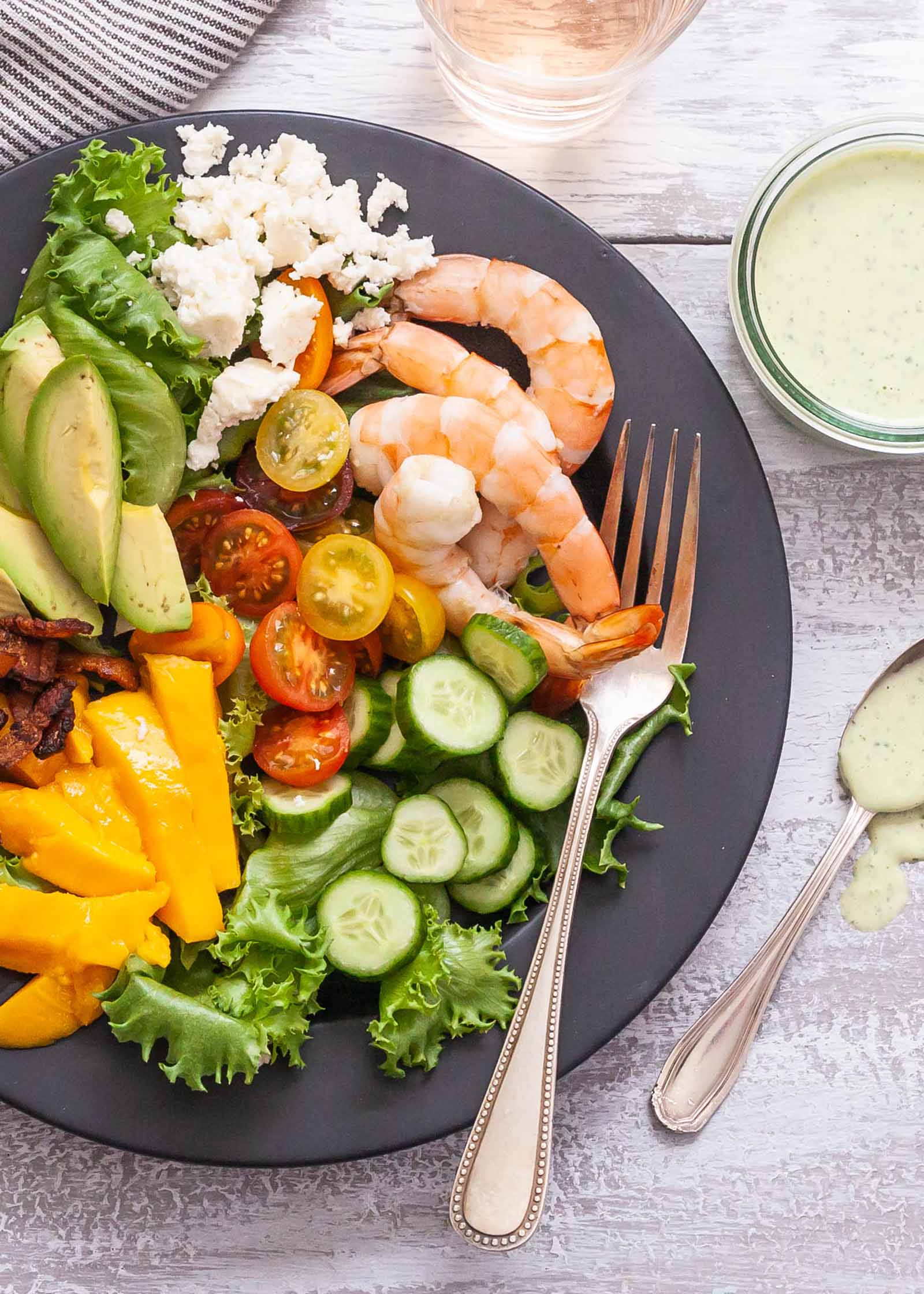 How to Make a Cobb Salad - shrimp and vegetables on gray plate with glass of rose