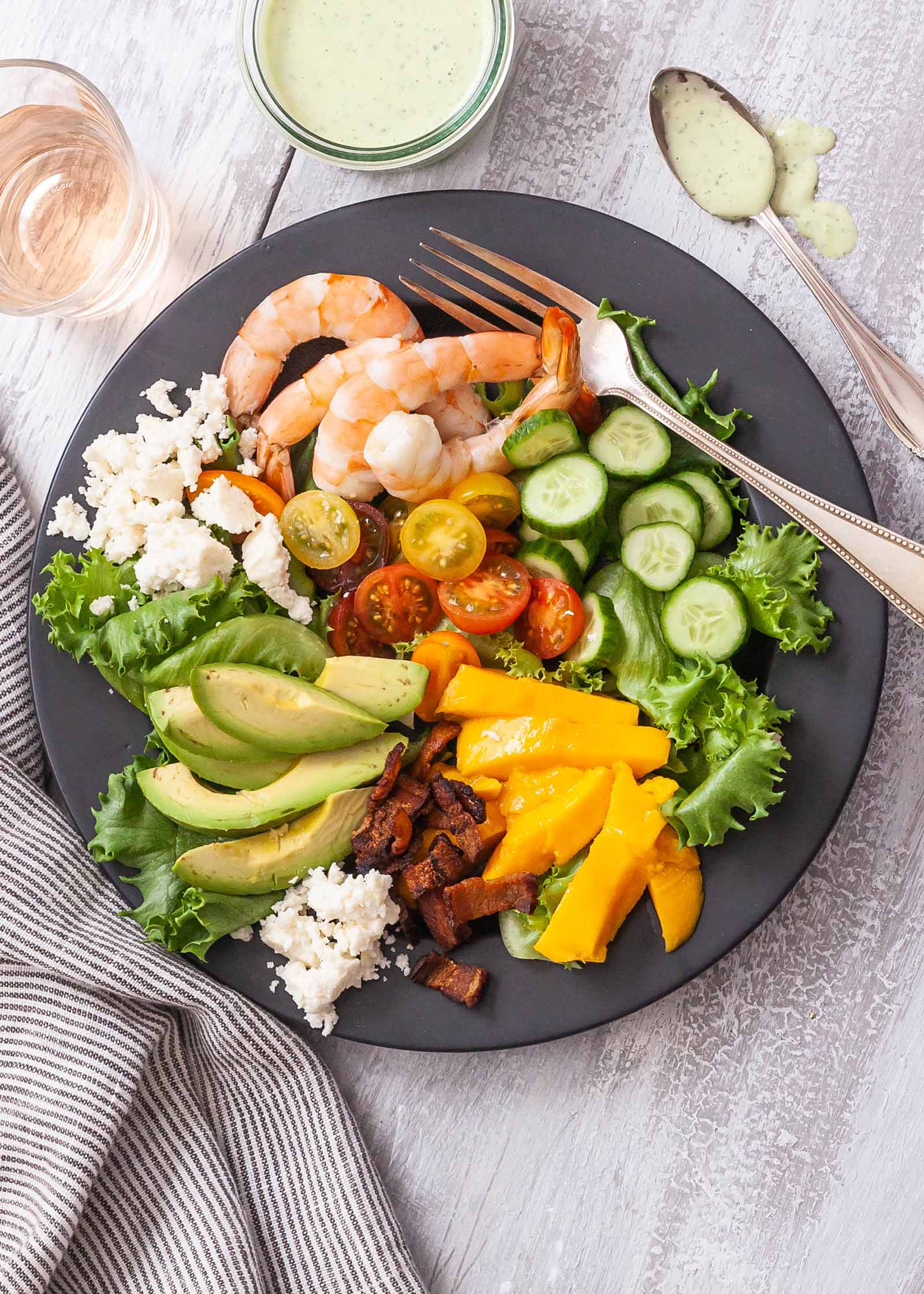 Cobb Salad with Basil Dressing - shrimp and vegetables on gray plate with glass of rose