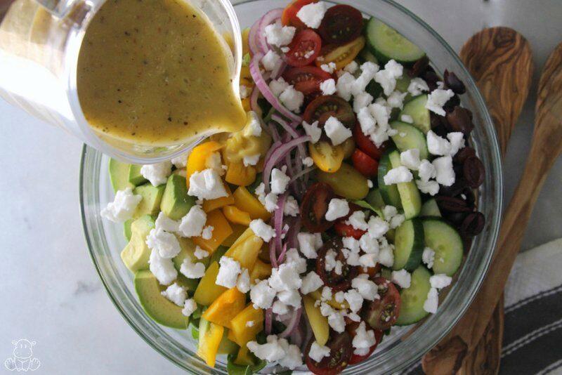 Pouring Greek salad dressing over vegetables