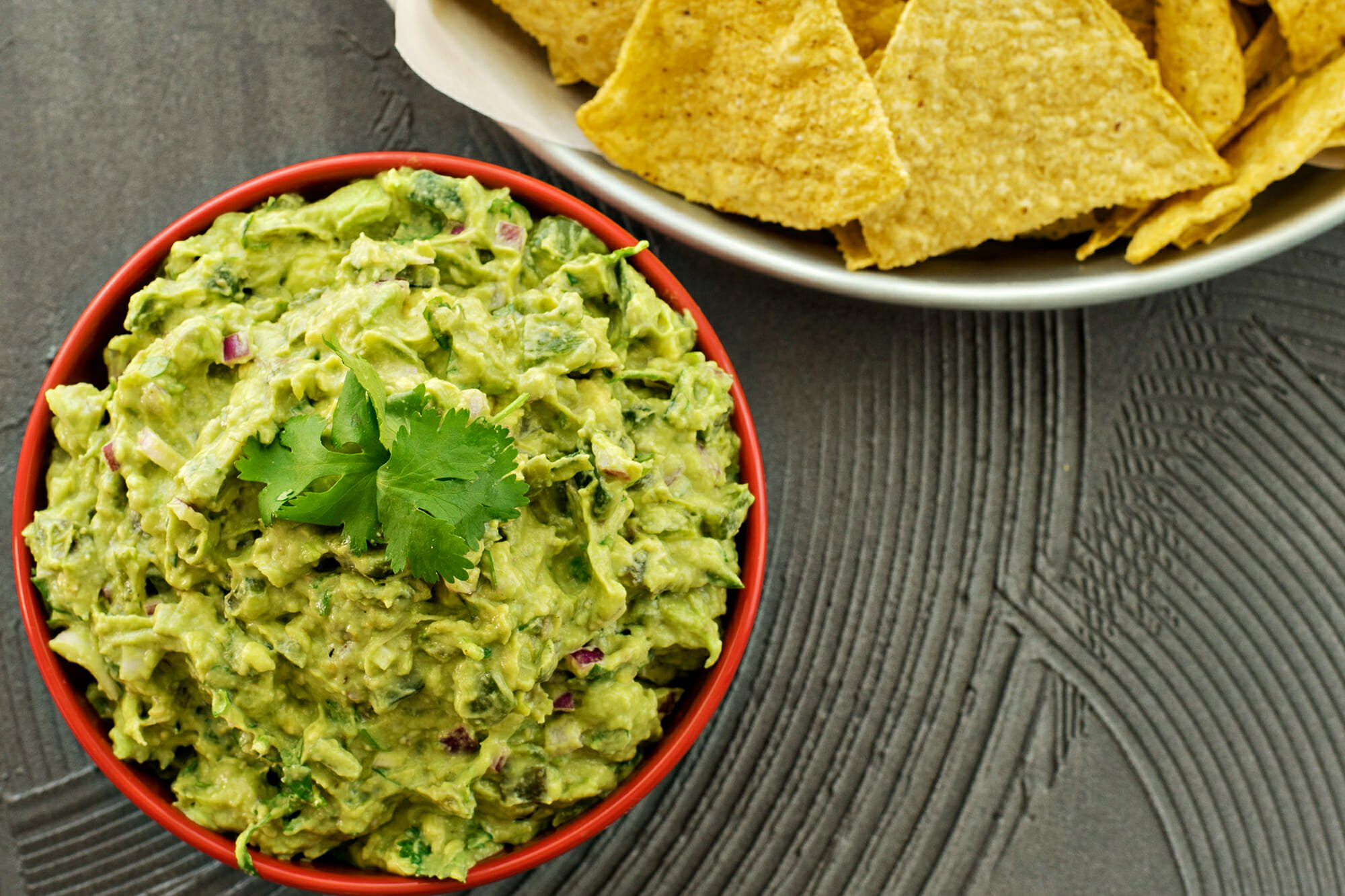 How to Make Avocado Dip - guacamole in a bowl wtih chips on the side