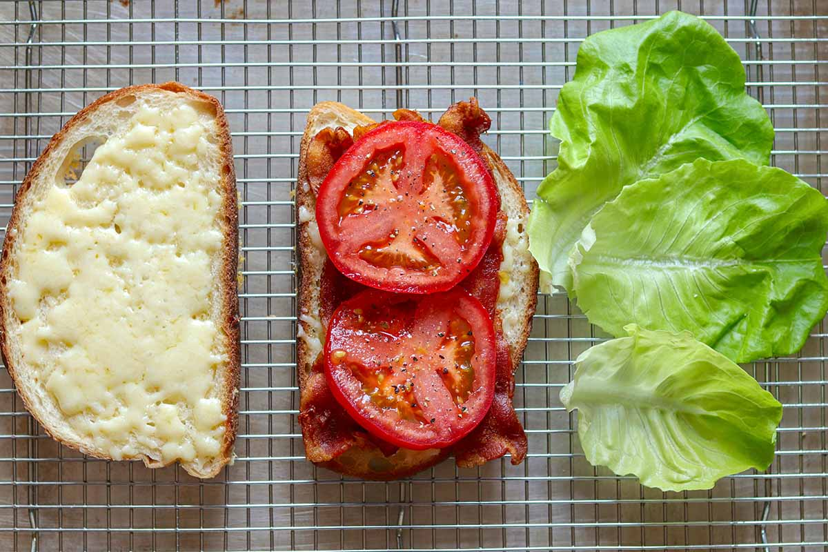 A slice of bread with cheese and a slice of bread with bacon and tomato and lettuce