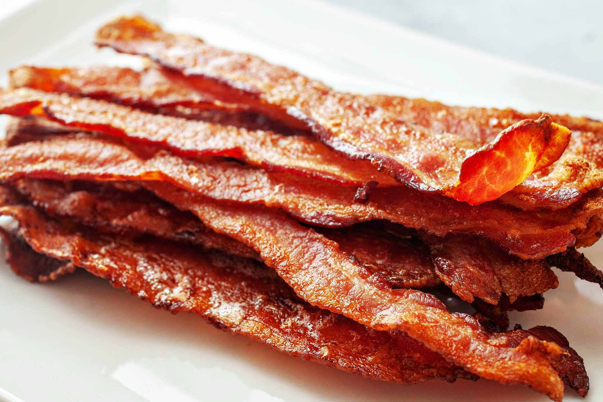 How To Bake Bacon in the Oven - pile of crispy browned bacon