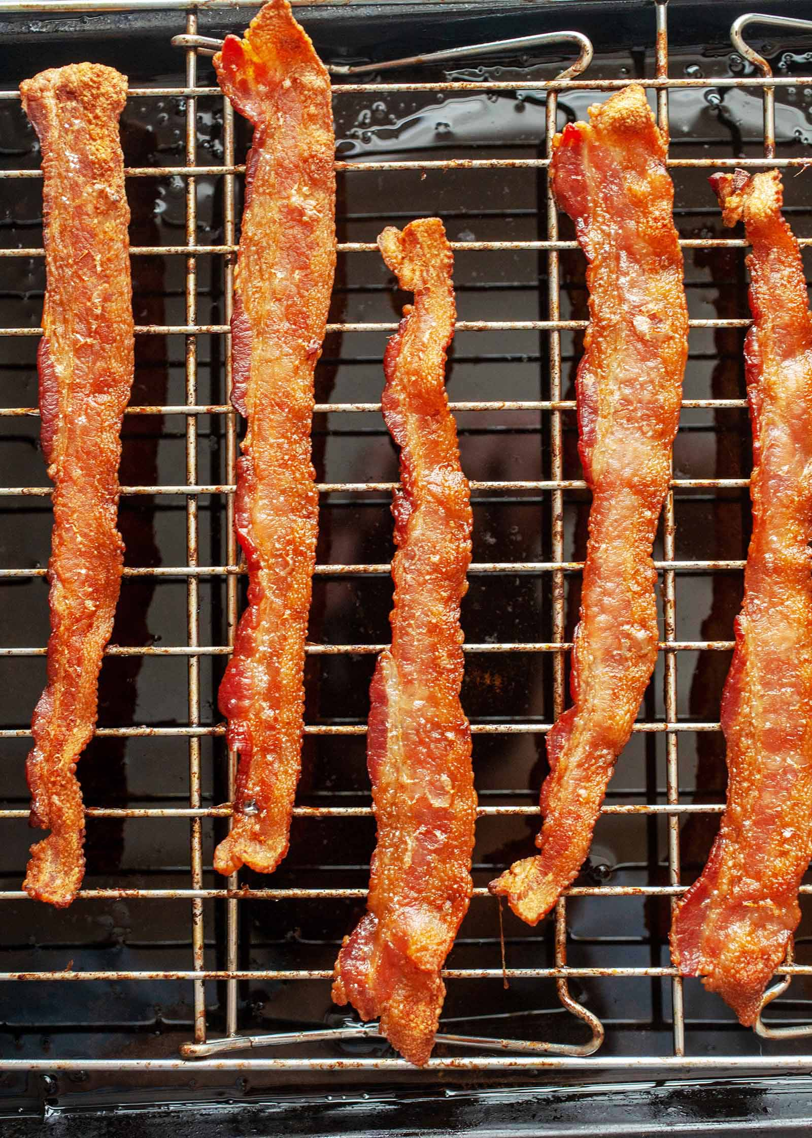 How To Cook Bacon in the Oven - five strips of browned bacon on rack