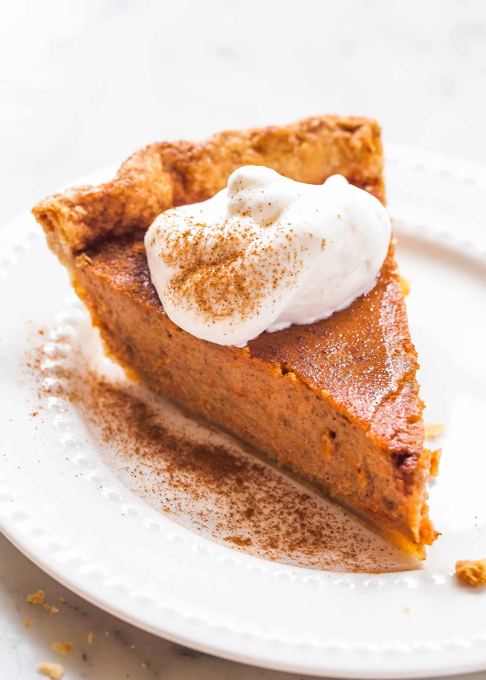 Slice of sweet potato pie on a white plate with whipped cream dusted with cinnamon and fork.