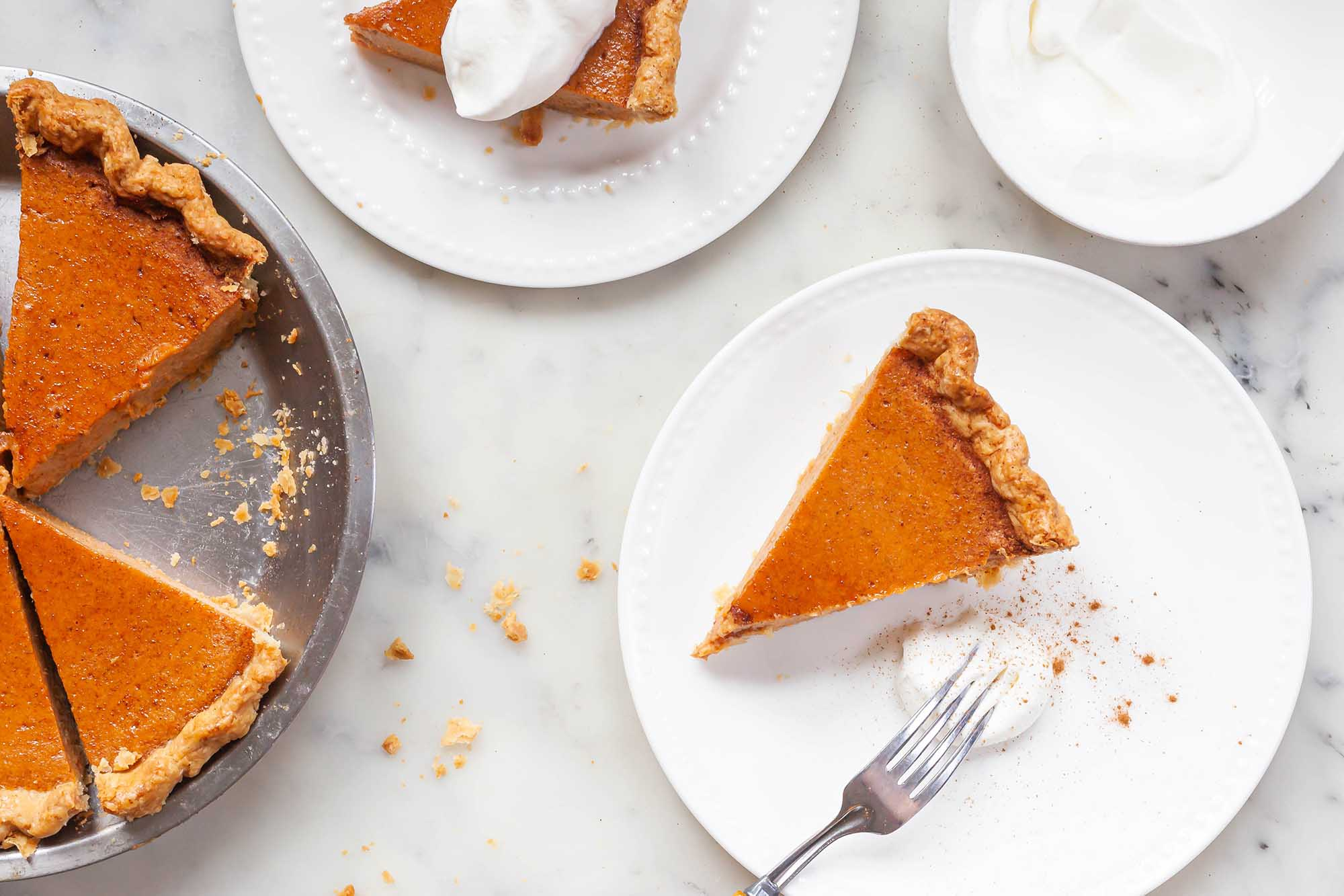 A couple of slices of classic sweet potato pie with the pie off to the side and some whipped cream