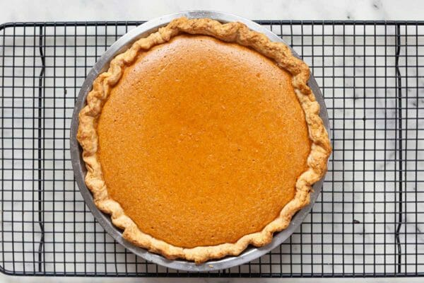 Whole classic sweet potato pie on a baking rack to cool.