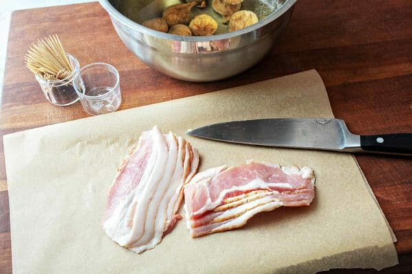 raw strips of bacon on parchment paper ready for bacon-wrapped figs appetizer