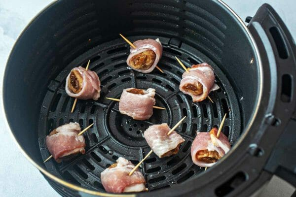 raw bacon-wrapped figs about to fry in an air fryer