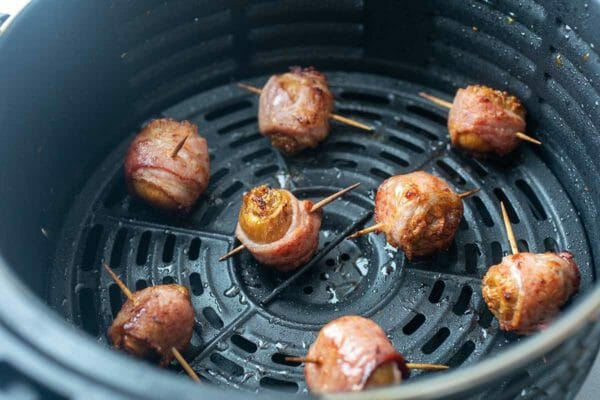 bacon-wrapped figs frying in an air fryer