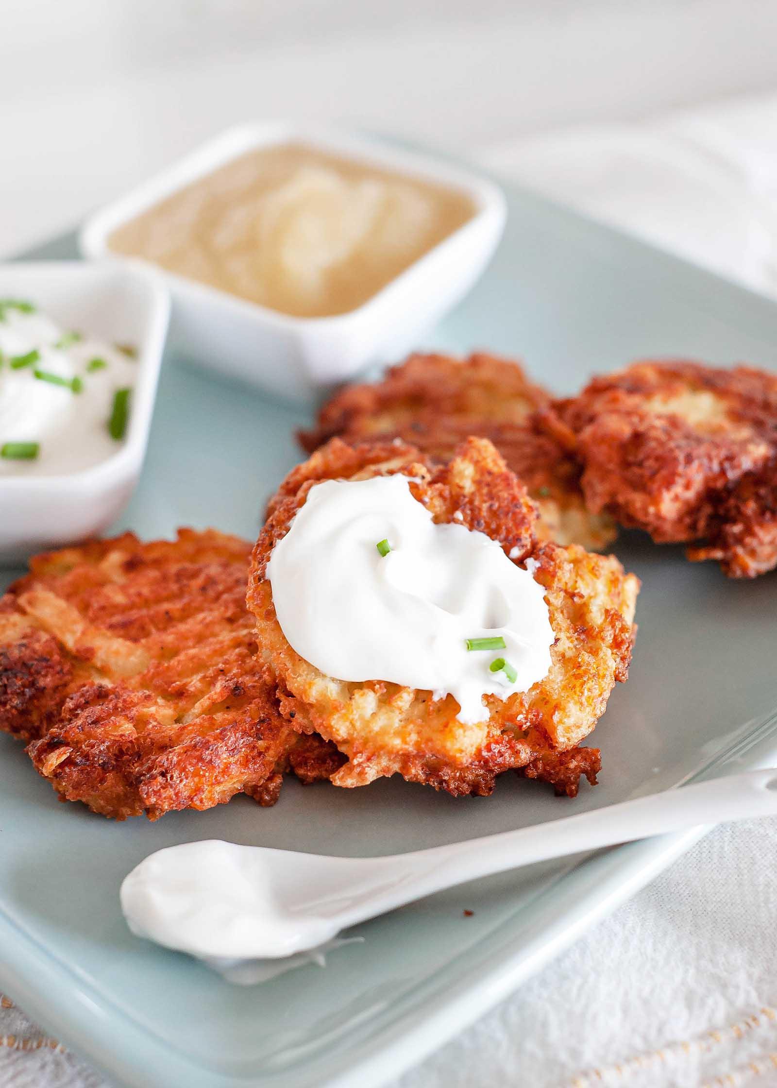 Easy potato latkes for hanukkah on a platter spread with sour cream