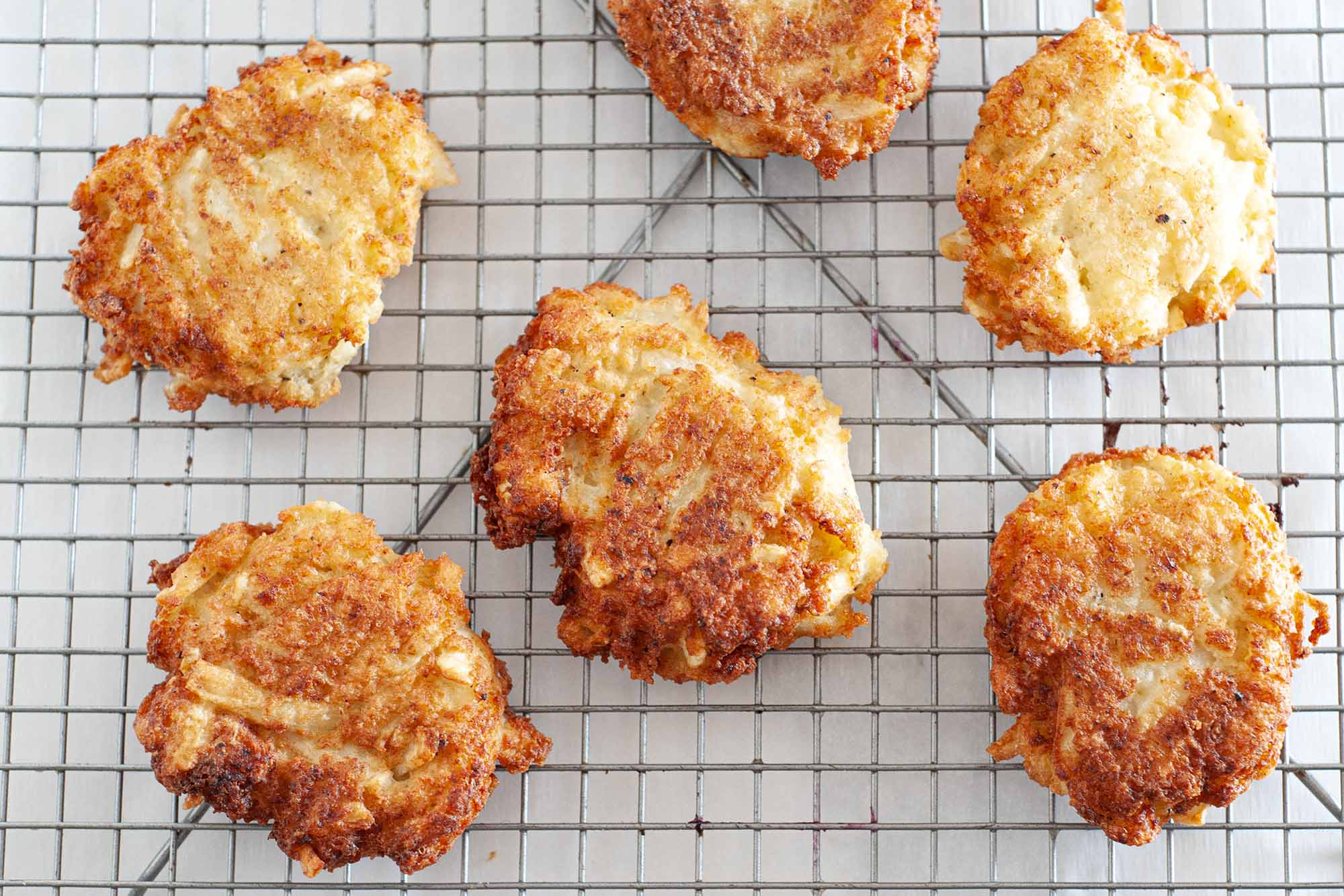 Fried potato latkes on a cooling rack