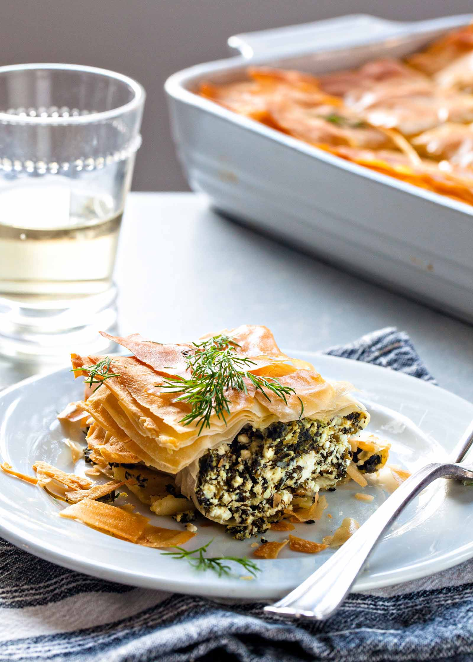 Slice of Greek Spinach Pie on a white plate, with a fork, a glass of white wine, and the casserole dish in the background,