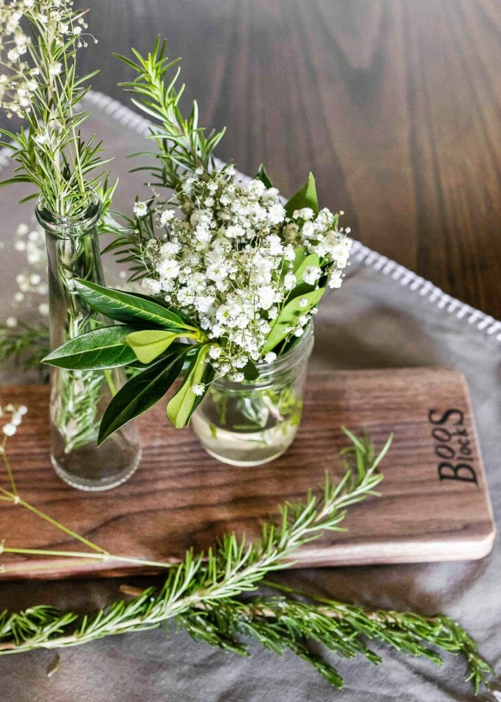 babys breath in mason jar on wood cutting board