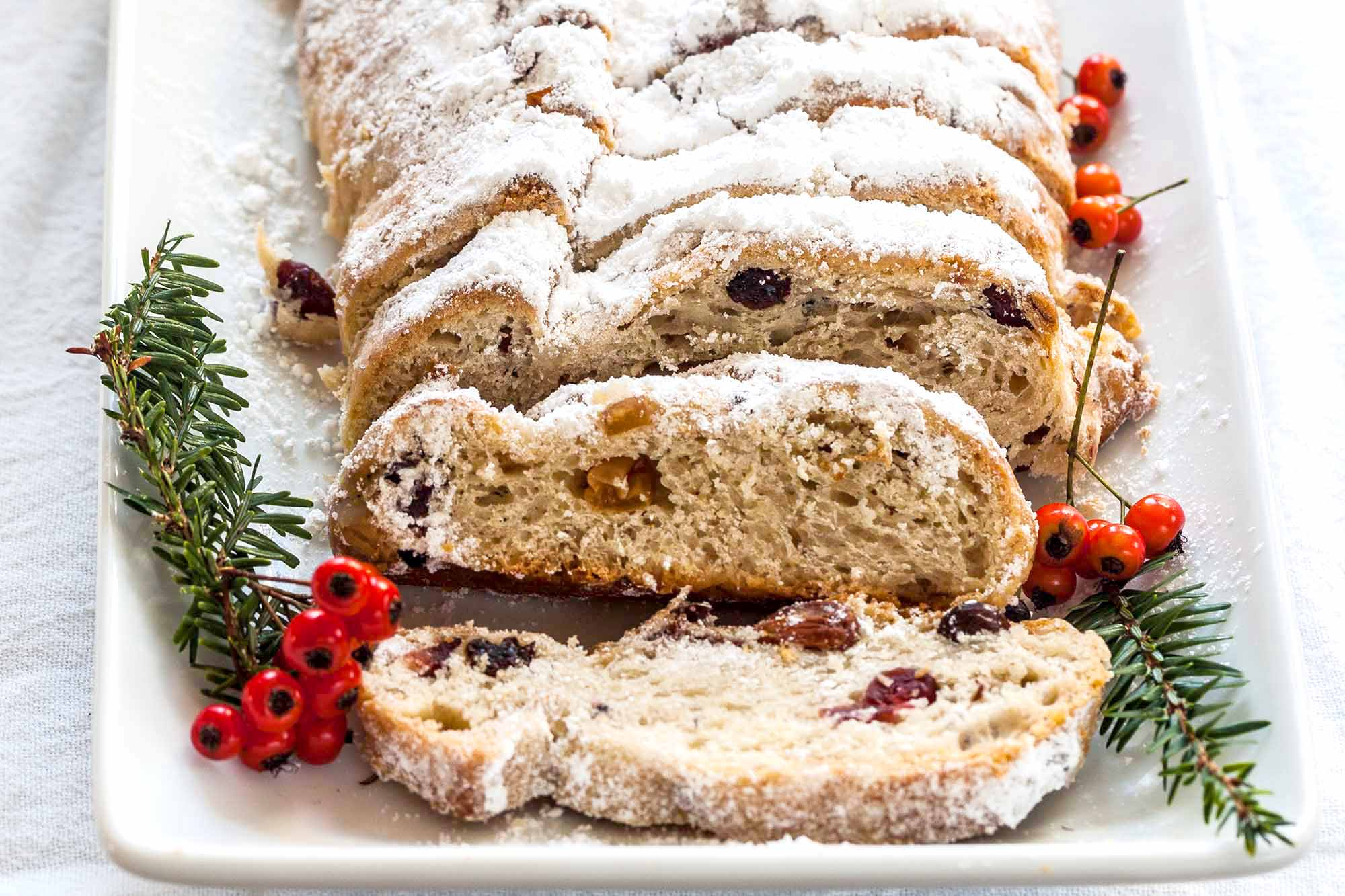 Stollen Christmas Bread filled with rum-soaked dried fruit coated with powdered sugar and sliced on a platter with a fine mesh sieve with powdered sugar with pine sprigs and berries nearby.