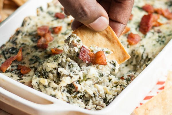 Best Spinach Artichoke Dip in a white dish with Bacon