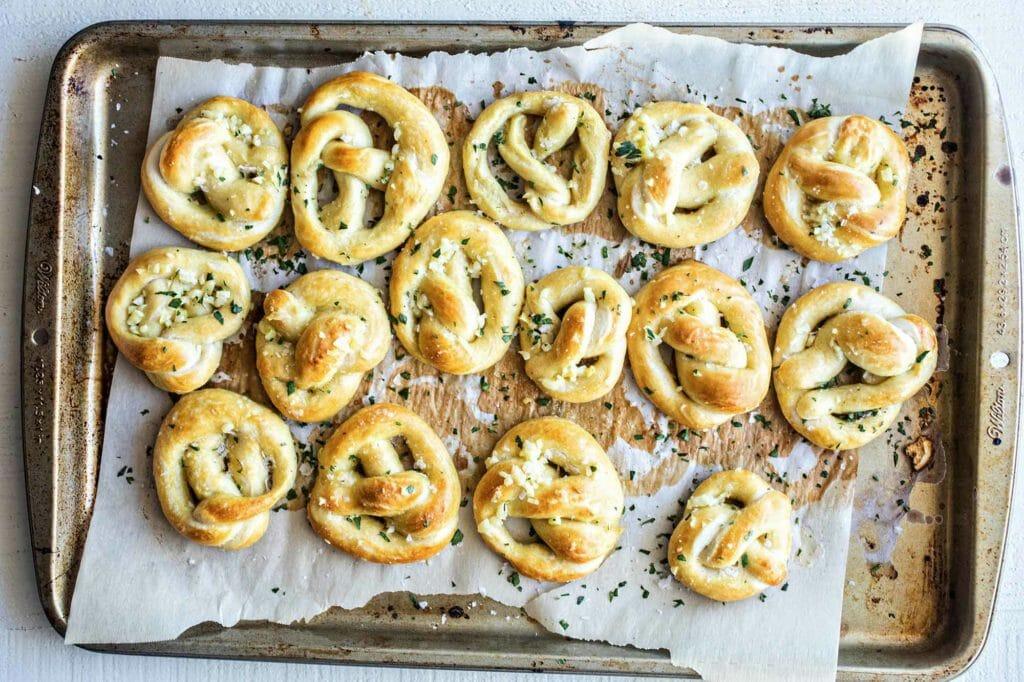 Mini garlic butter pretzels on a lined baking sheet