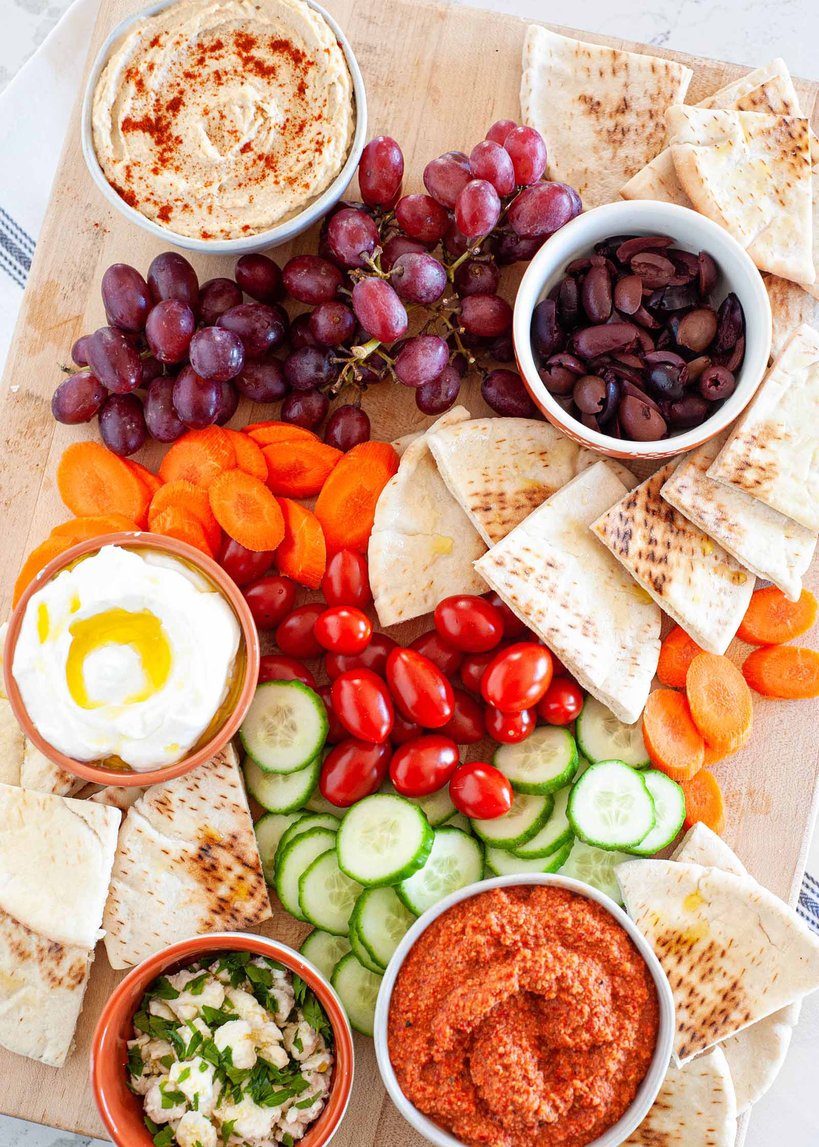 Mediterranean mezze platter with olives grapes vegetables pita