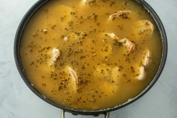 Chicken basting in broth for skillet chicken and rice