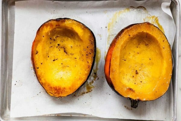 Roasted acorn Squash sliced in half on a sheet of parchment. The sliced half is facing up and sprinkled wiht salt and pepper.