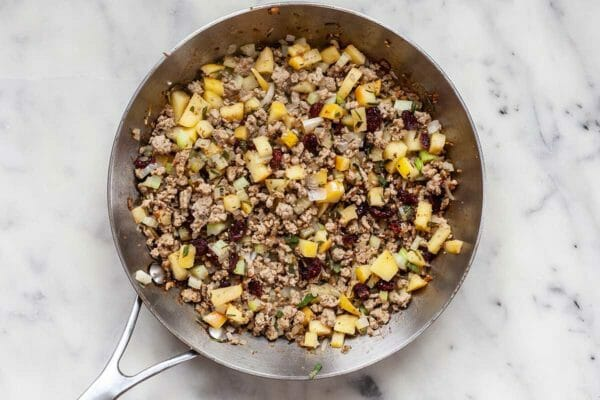 Ground turkey, rice and apples cooking in a skillet.