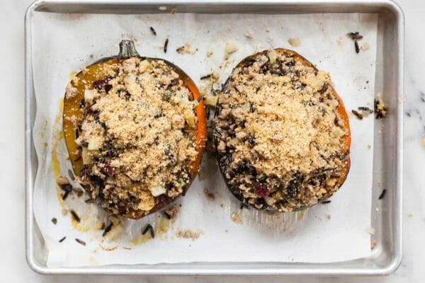 Two acorn squash halves filled with turkey, rice and apples and topped with breadcrumbs.