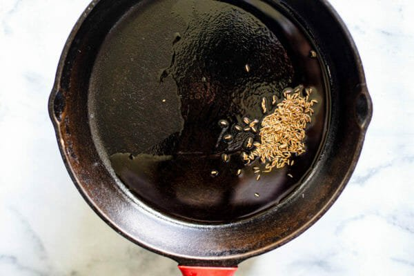Cumin seeds being toasted in a black skillet for vegetable samosa filling.