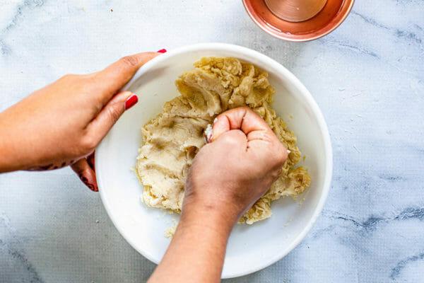 Woman kneeding the dough for samosas in a white bowl