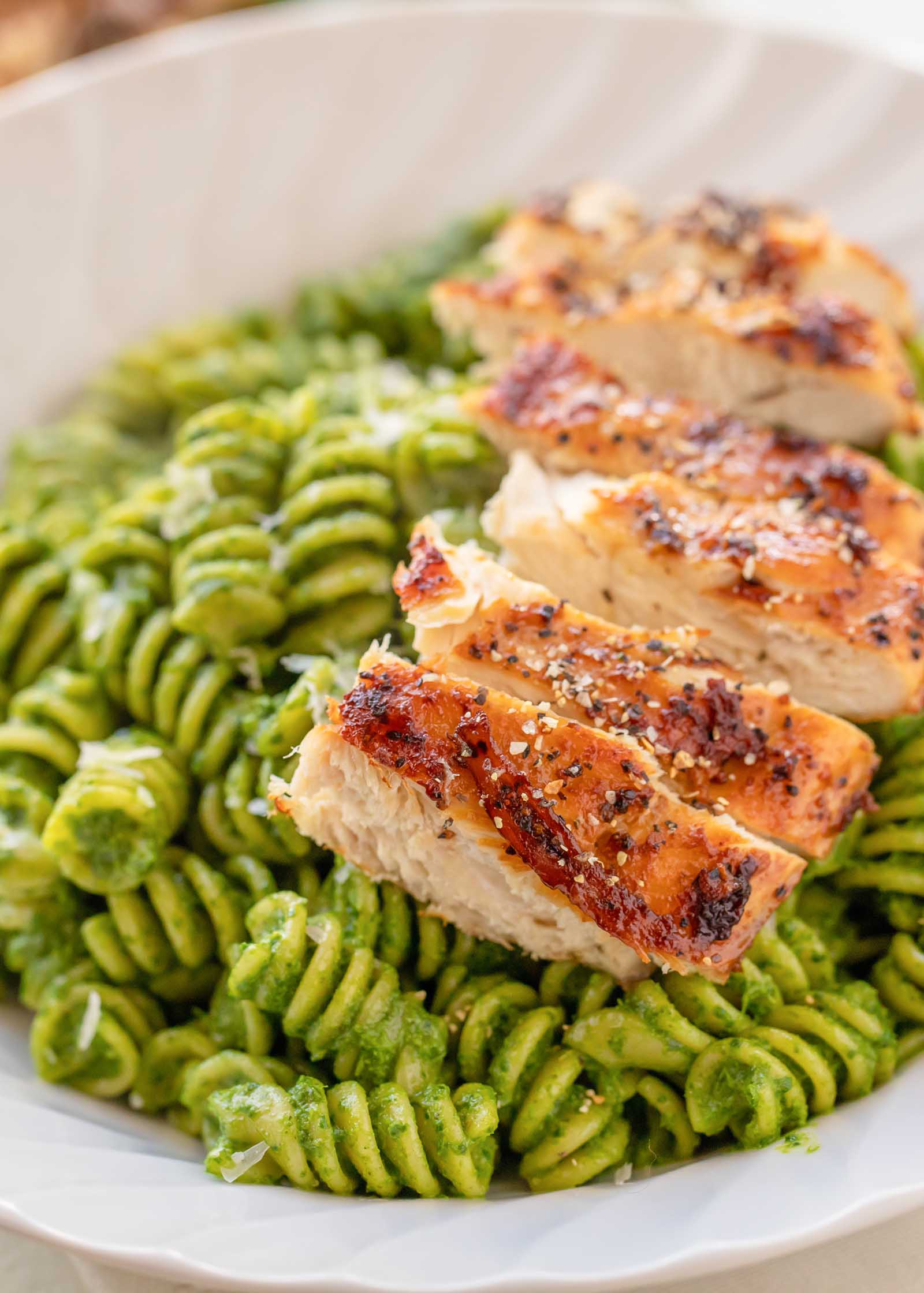 Close up view of easy rotini kale pesto in a white bowl. Roasted chicken breast is sliced and laid on the right side.
