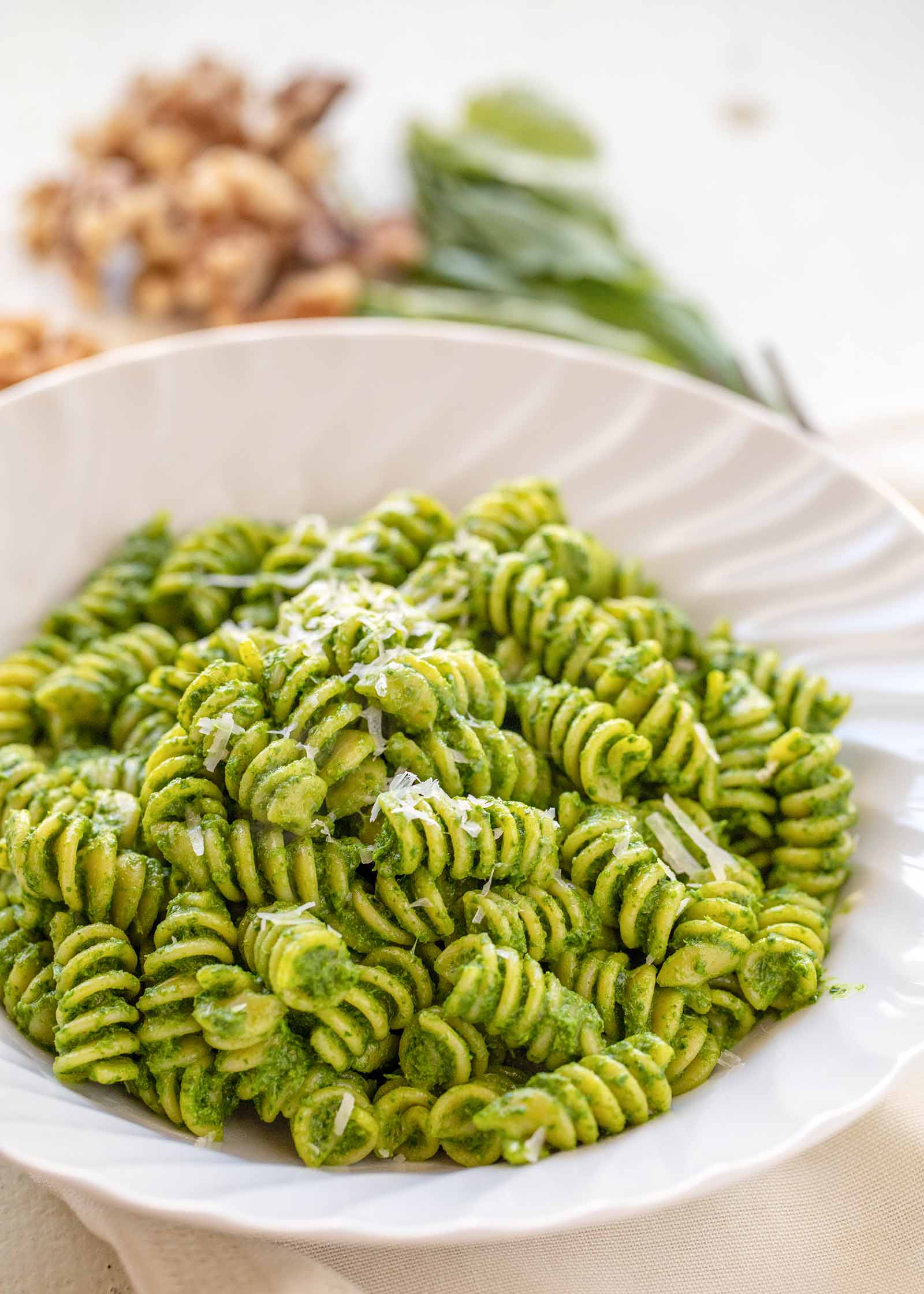 A white bowl with rotini and kale pesto inside. Walnuts and basil are in the background.