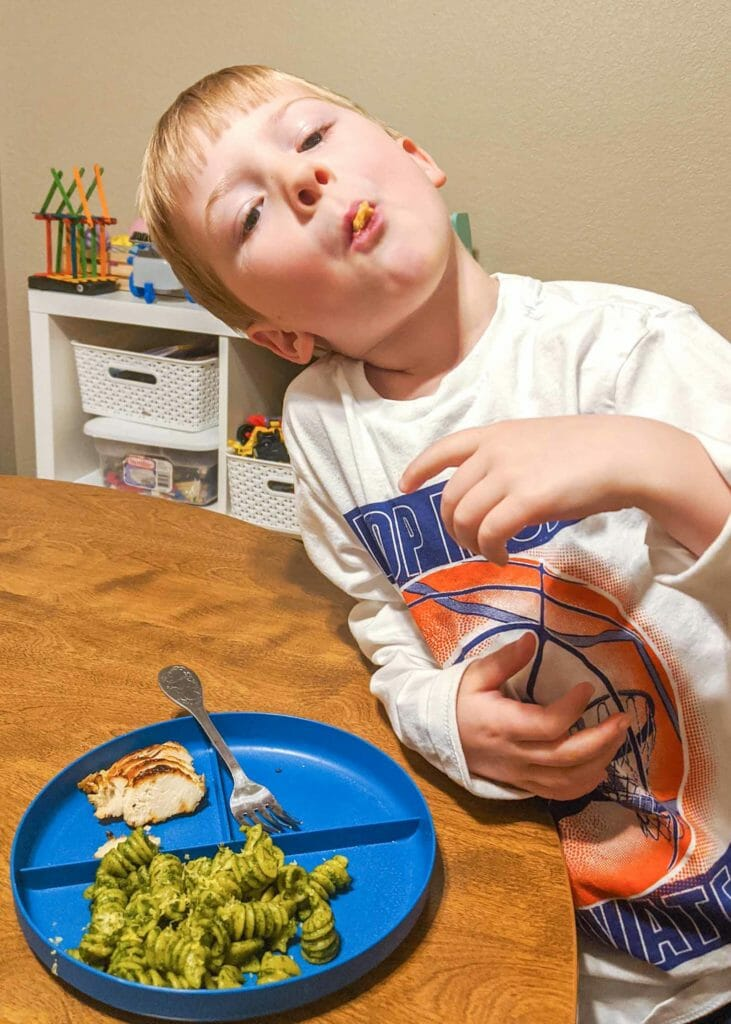 Young boy leaning on table with rotini in his mouth. A blue plate has some more easy kale pesto rotini on one side. A fork rests on another side of the plate next too small pieces of sliced chicken breast.