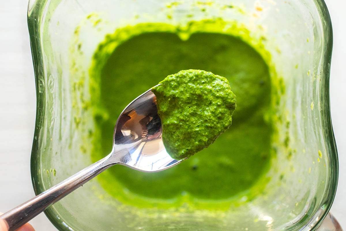 Top view of a spoon with kale pesto on it. The spoon is above a blender jar with more pesto inside.