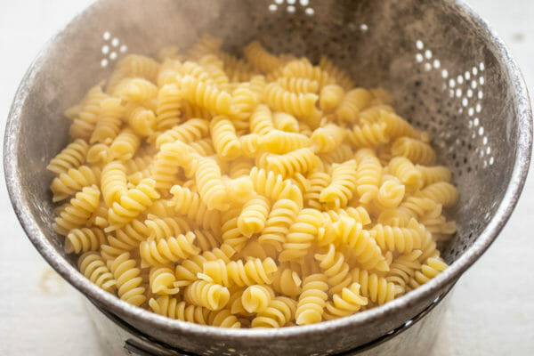 Steaming cooked rotini pasta draining in a colander.