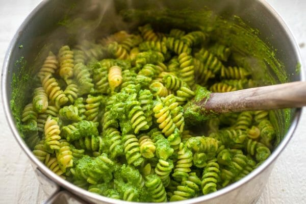 Large stockpot of weeknight rotini and kale pesto being stirred together with a wooden spoon.