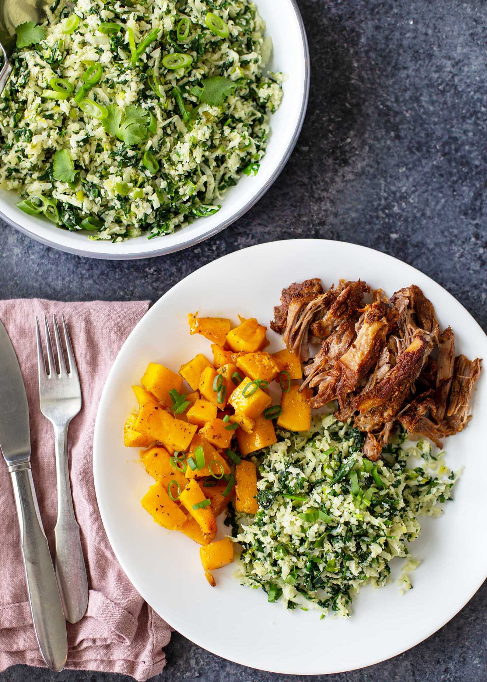 A white plate with healthy cauliflower rice with greens, shredded pork and chopped, roasted butternut squash. A pink linen with a fork and butter knife are to the left. A bowl of Green Cauliflower Rice is in the upper left with chopped scallions and cilantro visible along with the green rice.