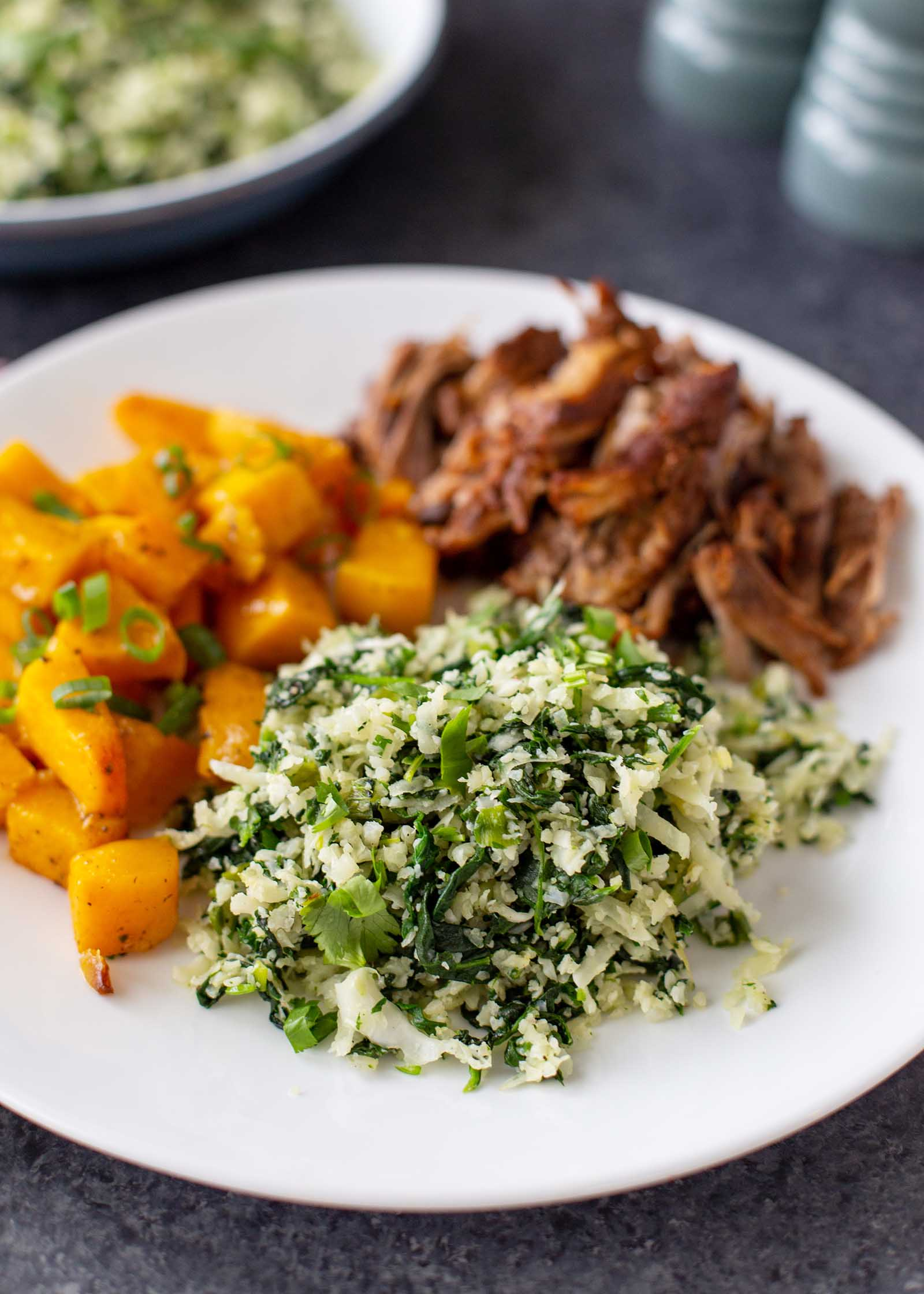 Close up view of a white plate on a slate background. The plate has vegan green cauliflower rice in focus. Roasted butternut squash and shredded pork are also on the plate. A partial view of a bowl of green cauliflower rice is in the upper left. Teal salt and pepper shakers are in the upper right.