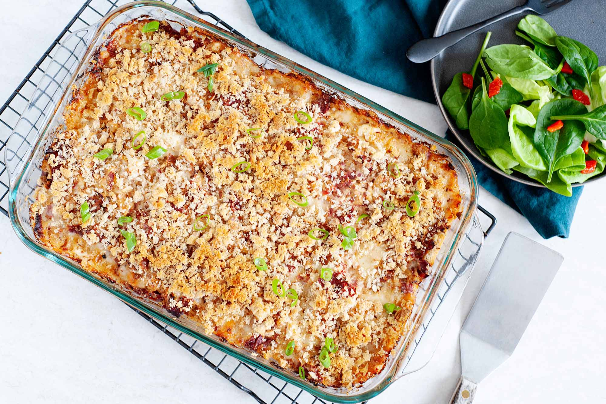 A golden brown baked reuben casserole is cooling on a rack. A metal spatula is in the lower right hand corner. A matte grey plate has a side salad and black fork in the upper right. A dark teal linen is under the plate.