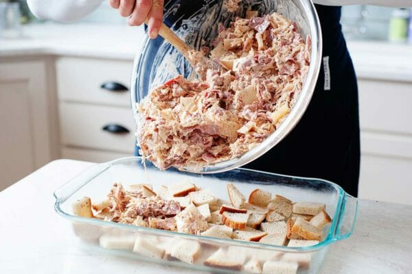 Reuben Casserole filling is being scooped onto the top of the chopped bread in the bottom of a glass casserole dish. The background is a kitchen and a marble topped island.