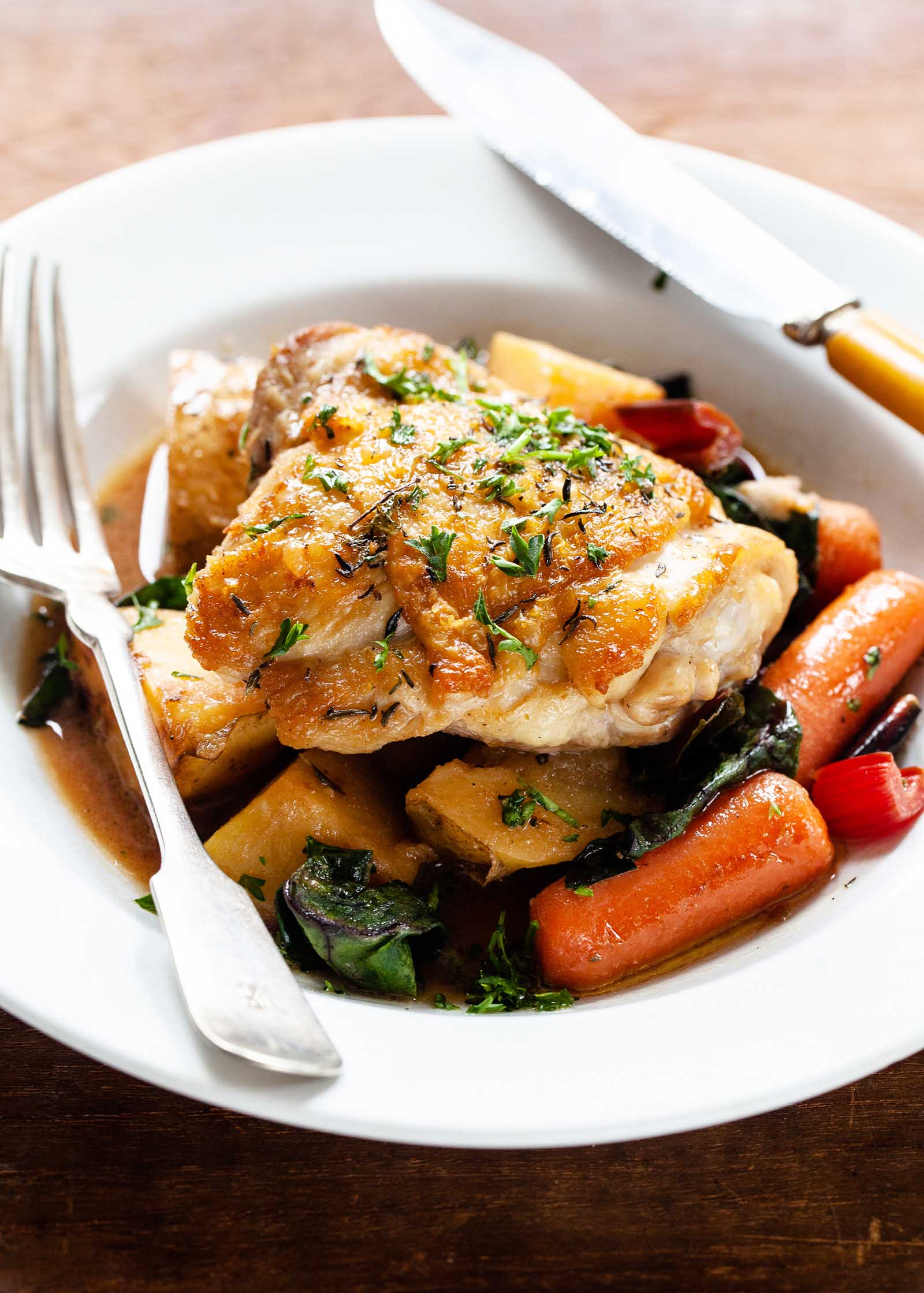A shallow white bowl has one crispy chicken thigh covered in herbs. Baby carrots, wilted chard and chopped potatoes with a broth at the bottom are in the bowl. A knife is on the right side and a fork is on the right side of the bowl.