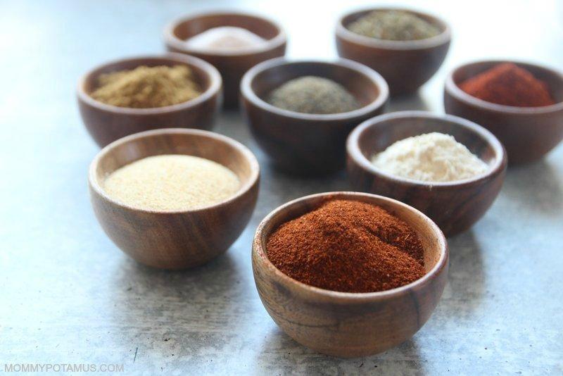 Individual spices in bowls (chilli powder, onion powder, garlic powder, paprika, oregano, cumin, salt and pepper)