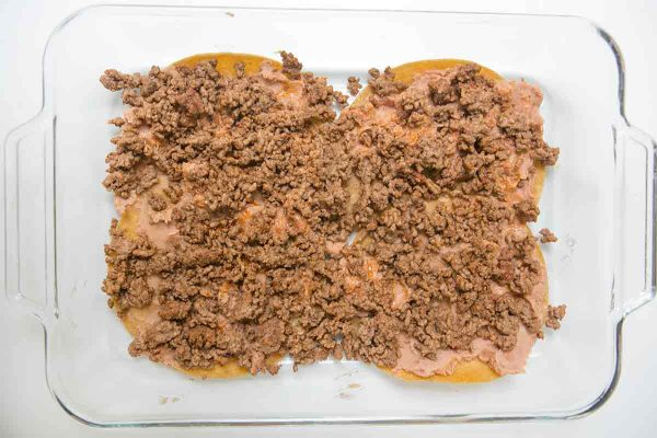 To make mexican lasagna, add a layer of ground beef on top of the beans