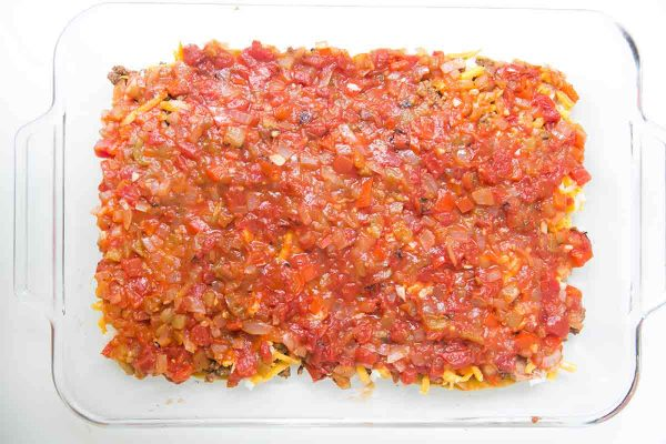 To make mexican lasagna, spread half the sauce over the beans, beef, and cheese