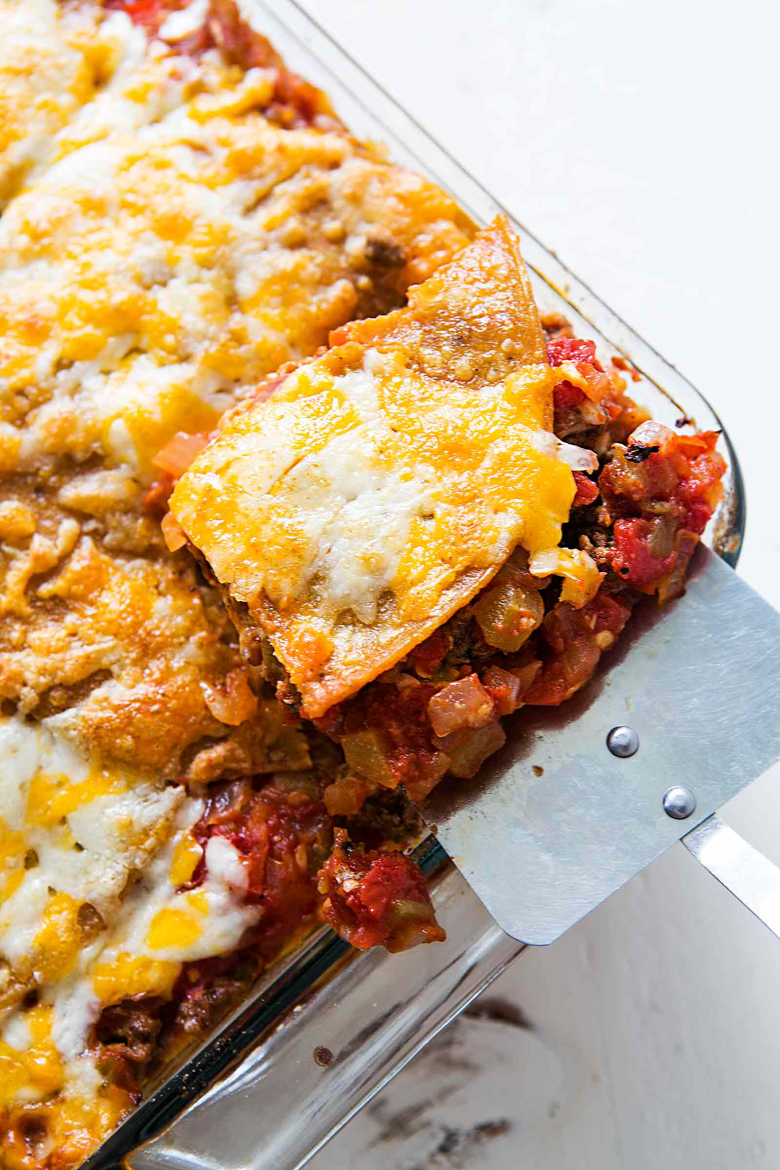 Sliced taco lasagna made with tortillas, beans, beef, tomatoes, and cheese in a baking dish