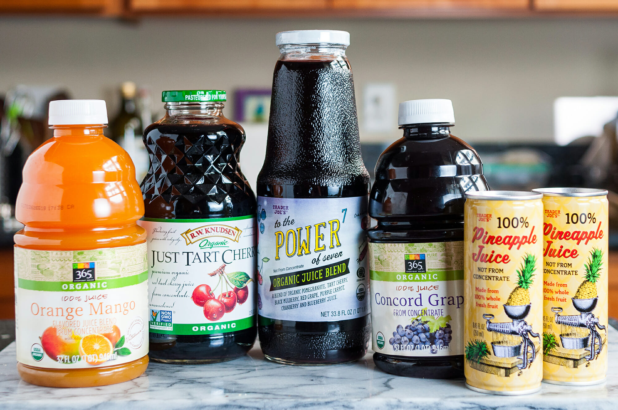 Several bottles of store-bought juice on a counter