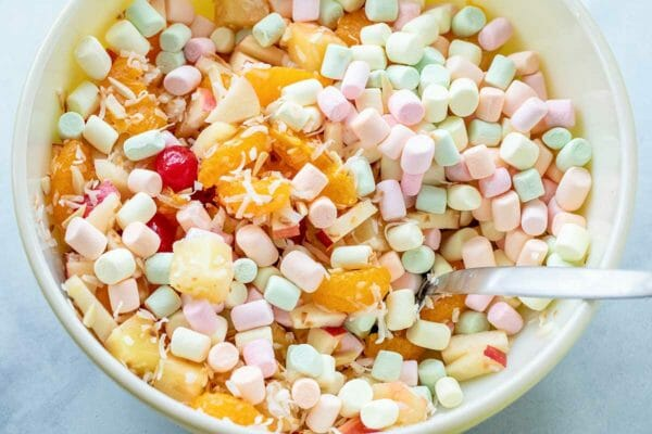 A mixing bowl with colorful mini marshmallows, mandarin oranges, shredded coconut and chopped apples for an Easter fruit salad.