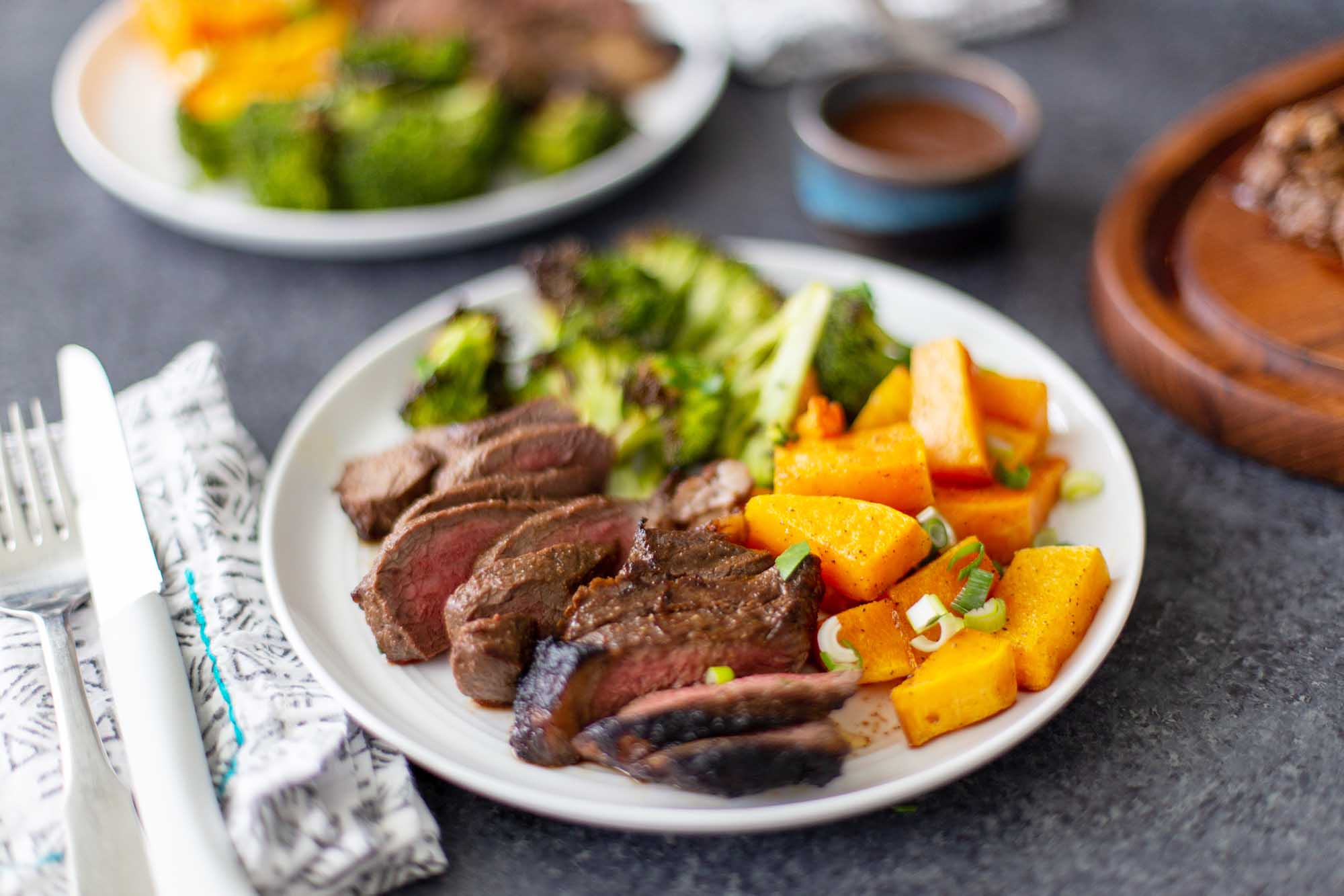 Side view of two plates with sliced easy broiled steak, chopped broccoli and squash. Silverware and a linen are next to each plate.
