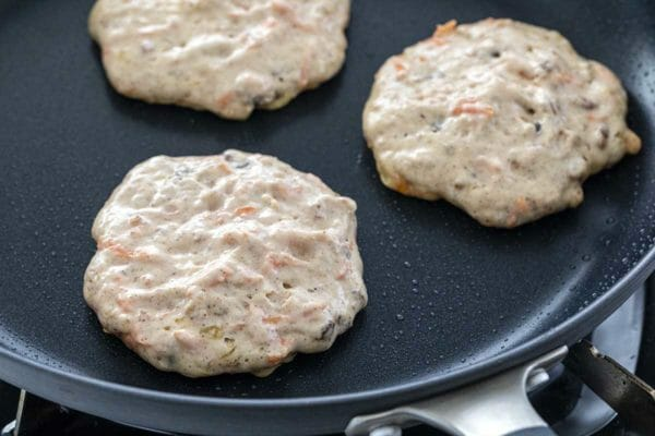 Three carrot cake pancakes are cooking in a non-stick pan. The edges are firm but the top is still wet.