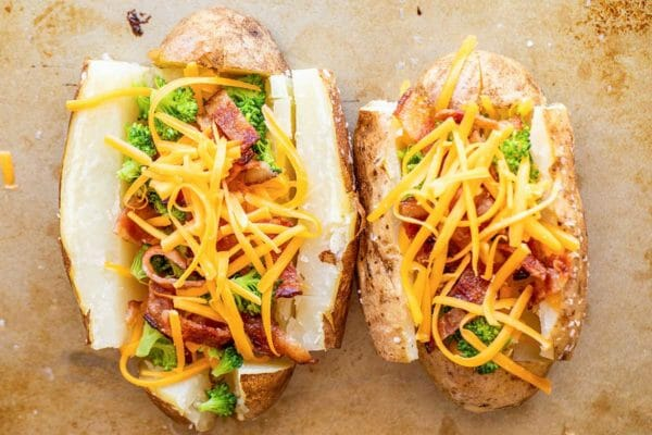 Two loaded baked potatoes with bacon on a worn baking sheet. The russet potatoes are split open with broccoli, chopped bacon and unmelted, shredded cheddar cheese.