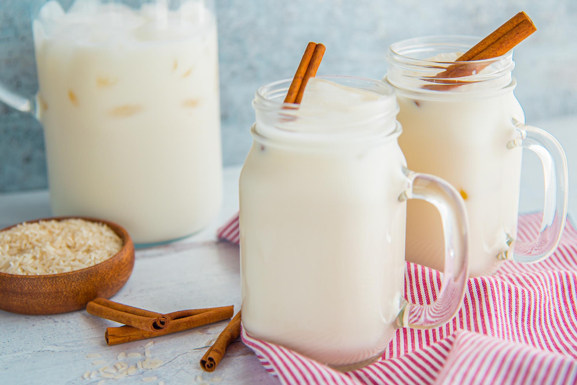 A large mason jar of easy homemade horchata with a cinnamon stick inside is in front of a similar glass and a pitcher of homemade horchata. A small bowl of rice and cinnamon sticks are to the left.