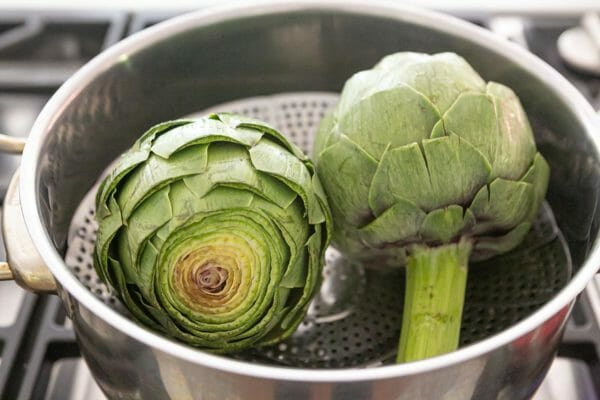 Arrange the artichokes in a steamer basket to cook