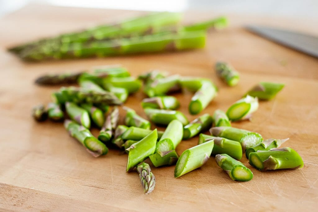 chopped asparagus on a cutting board